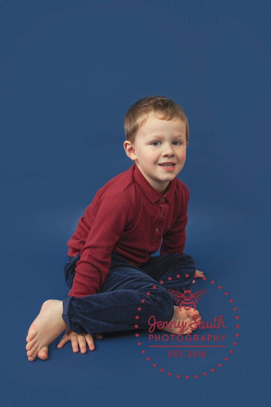 A little boy sits against a navy blue background for a portrait session