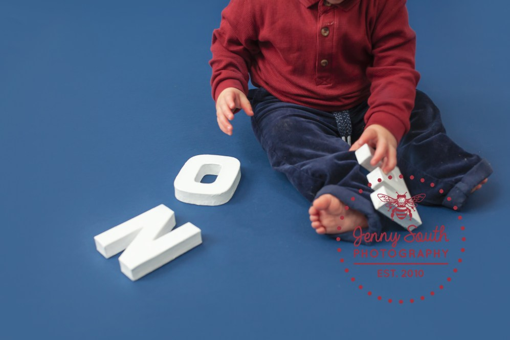 Little baby plays with white letters to spell out one.