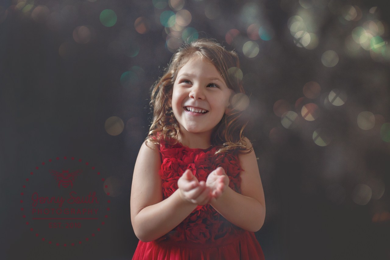 A little girl smiles joyfully wearing a red dress. Glitter floats in the air all around her.