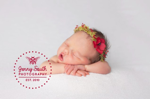 A baby girl sleeps on her hand against a white backdrop wearing a flower crown containing poppies.