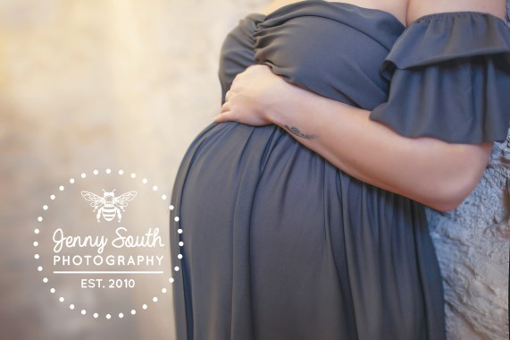 An expectant mother cradles her growing bump in a grey maternity gown.