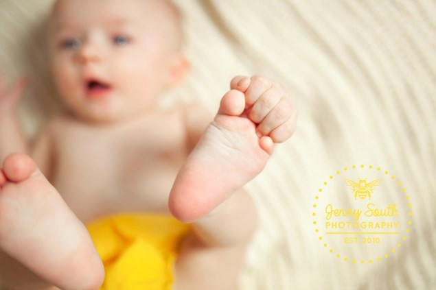 A baby plays with their feet during a milestone session in a photography studio