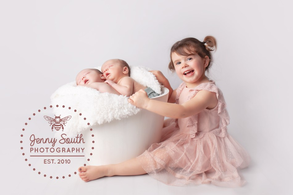A proud big sister shows off her brand new twin baby brothers during a photo shoot in Plymouth