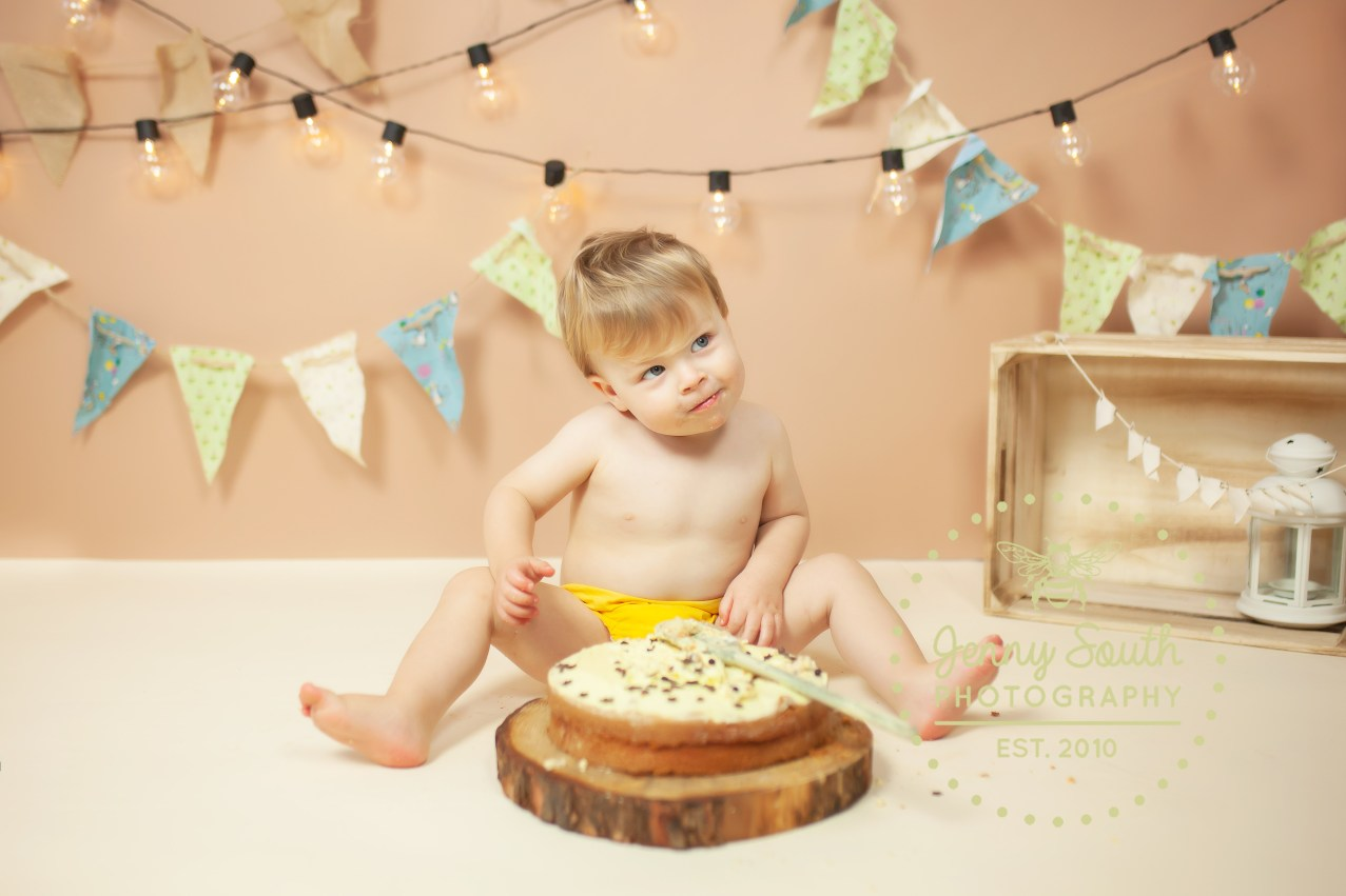"""A Cheeky little boy looks to his mother in wonder like """"can I really smash this cake?!"""""""