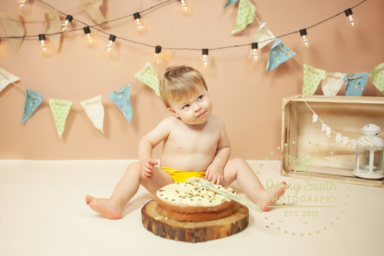 "A Cheeky little boy looks to his mother in wonder like ""can I really smash this cake?!"""