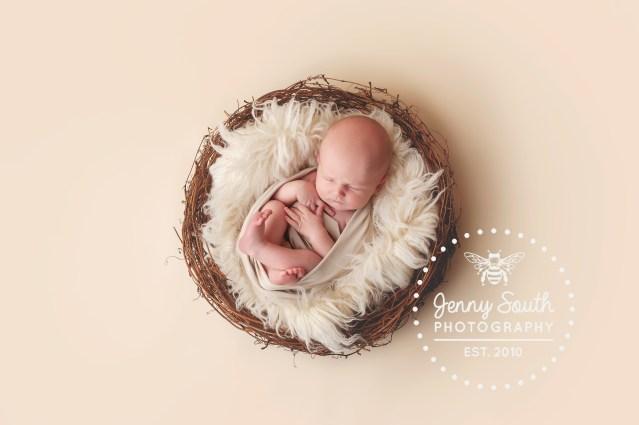 A baby boy sleeps in a fur nest against a cream backdrop.