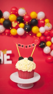 A Mickey Mouse birthday cake sits on a white cake stand with a coordinating cake topper to complete the theme.