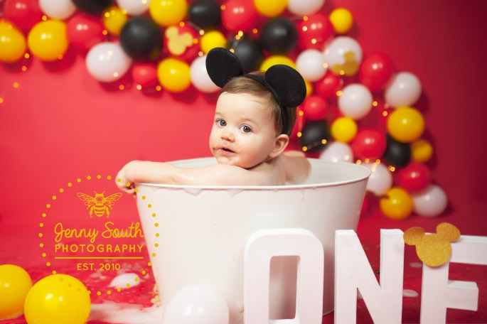 A little boy looks over his shoulder whilst sat in a tin bath tub during his Cake smash session