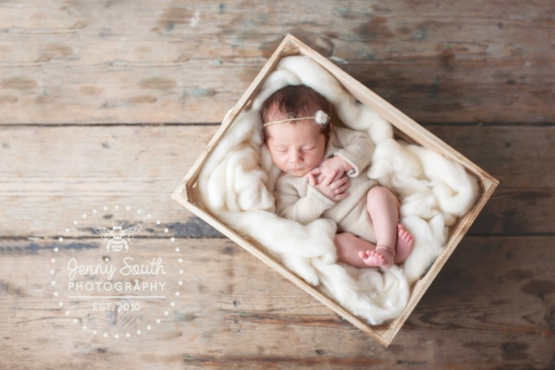 A newborn baby lies comfortably upon a bed of natural wooden texture. Against the rugged wooden floorboards