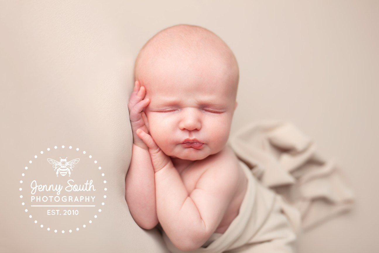 An 11 day old newborn baby boy sleeps on his hand against a cream backdrop