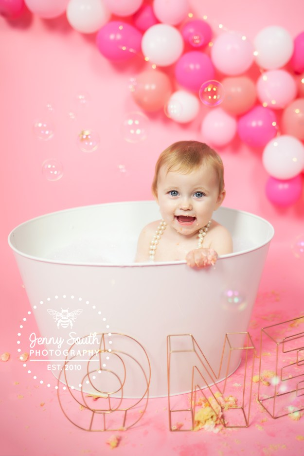 A baby sits in a tin bathtub after her cake smash session for her first birthday.