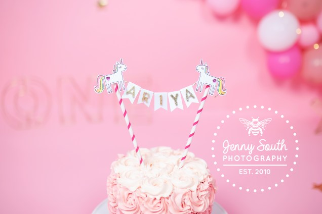 A Magical girly themed pink cake with a unicorn cake topper sits against a pink balloon wall for a little girls cake smash.