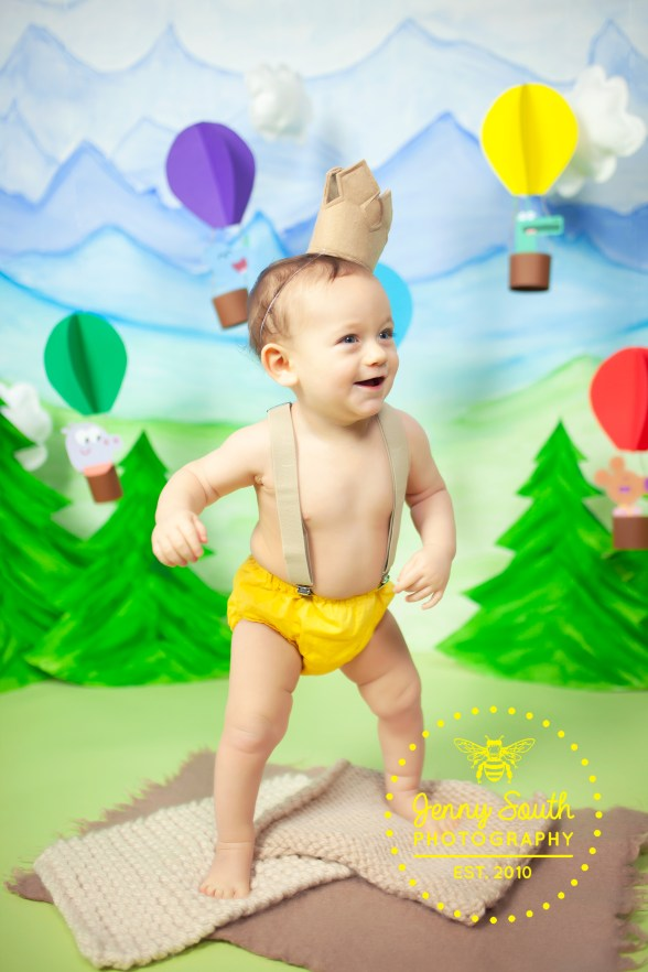 A baby boy is taking his first steps just before he turns one during his cake smash photo shoot in Plymouth