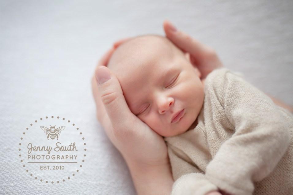 A newborn baby is cradled in her daddies hands.