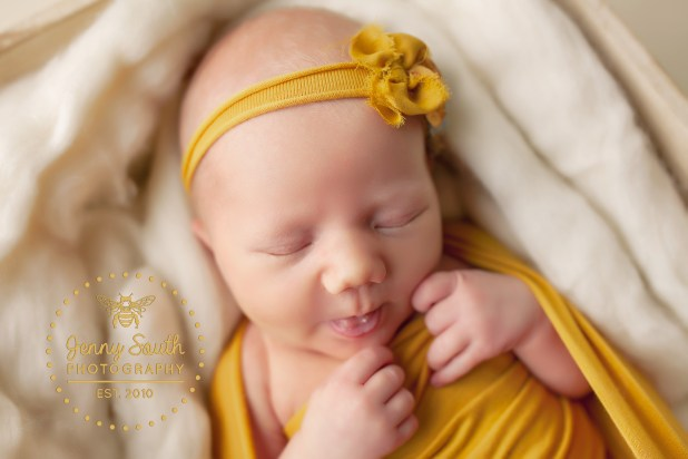 A Little girl just 14 days old sleeps wearing a floral head band in yellow