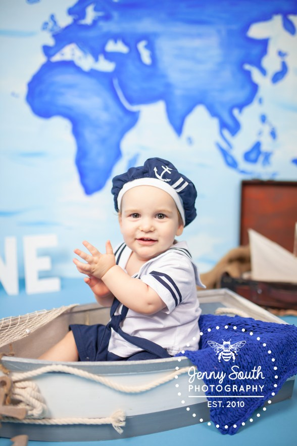 A baby Boy sits in a boat during a nautical cake smash for his first birthday.