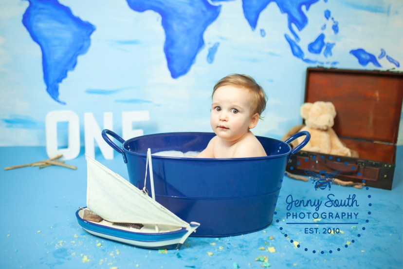 A baby boy sits in a metal bath tub after his first birthday cake smash.