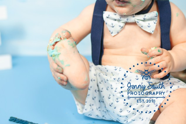A baby holds his foot which is covered in icing during his nautical cake smash photography session.