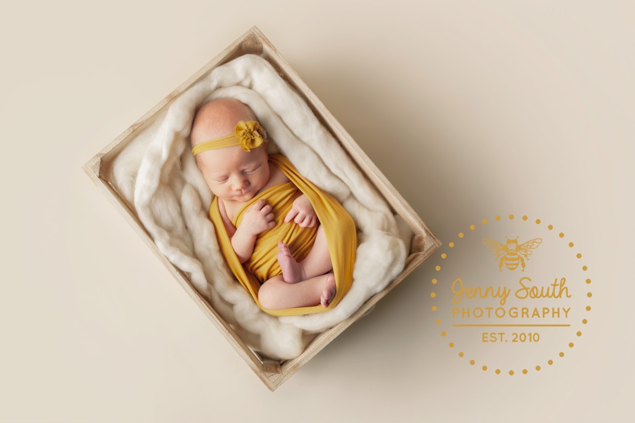 A baby girl sleeps soundly wrapped in a yellow mustard wrap and floral headband, in a wooden Crete on a cream backdrop