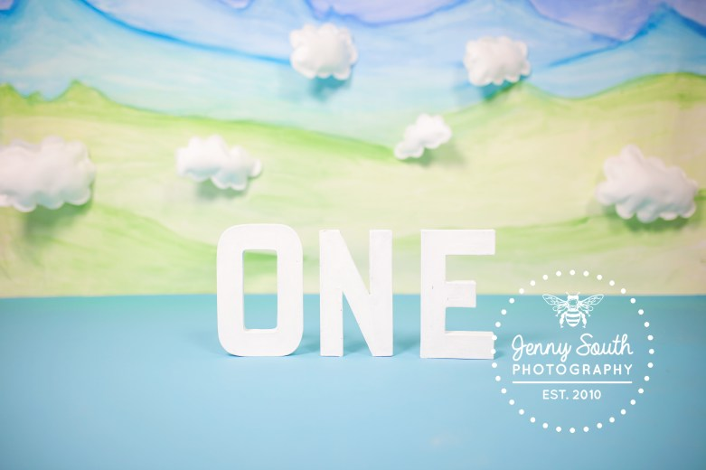 White letter spelling the word one surrounded by white fluffy clouds and a handprinted backdrop of blue and green mountains.