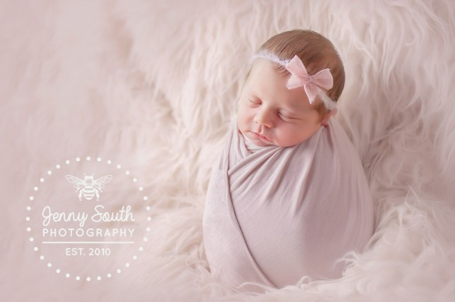 A Newborn baby girl sleeps soundly in a matching pink wrap and headband.
