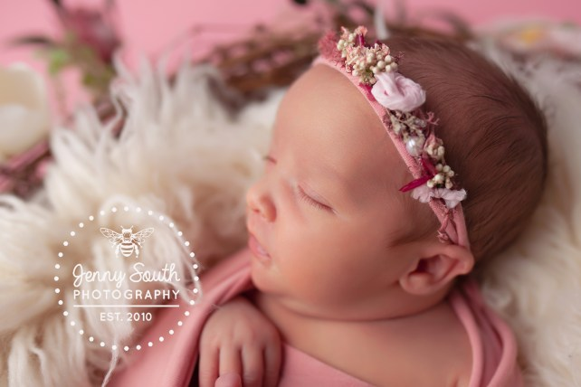 A newborn baby sleeps surrounded by floral's and fur during her first photo shoot