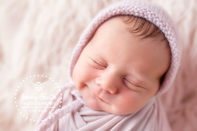 A baby girl smiles in her slow whilst posing for newborn photos.