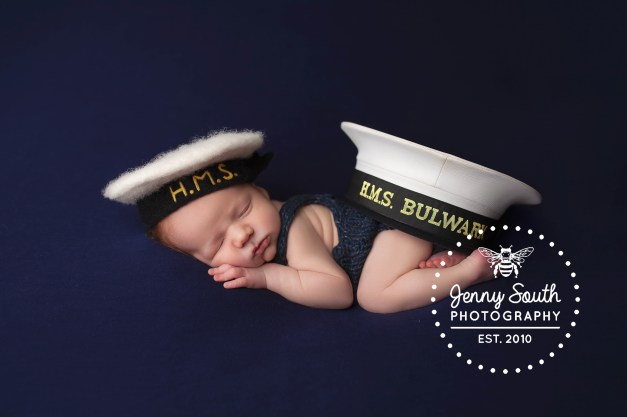 A baby boy sleeps with his Daddies Royal Navy cap covering his bottom.