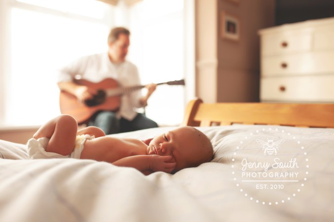 A father strums a gentle time on his guitar as his sleepy newborn son listens on the bed in front of him