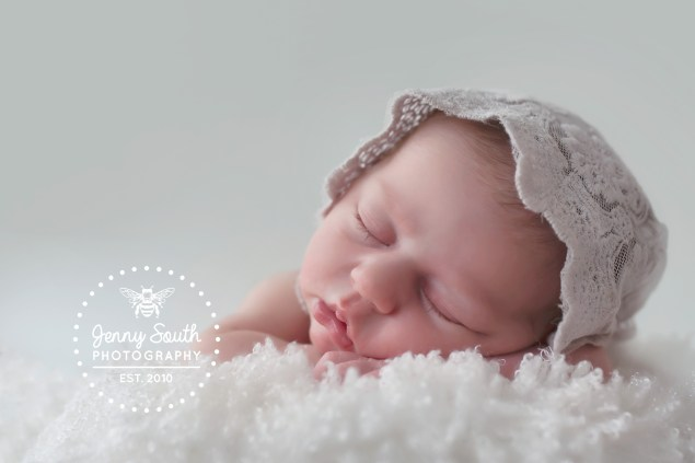 A dreamy new baby girl sleeps soundly against a grey background with a delicate lace bonnet upon her head.