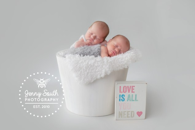 A wonderful set of twins pose sweetly in a white bucket on a grey backdrop for their newborn photo shoot