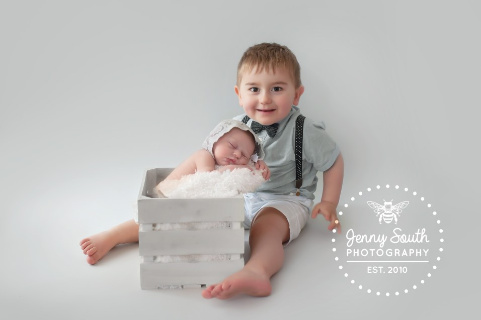 A proud big brother shows off his newborn little sister during a newborn photo shoot.