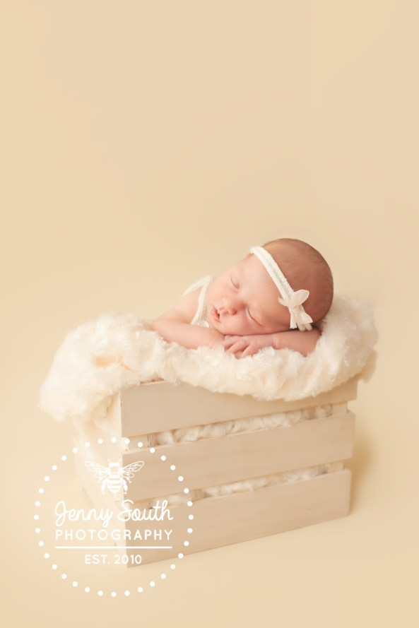 A beautiful newborn bundle sleeps soundly in a cream wooden create on a soft textured blanket