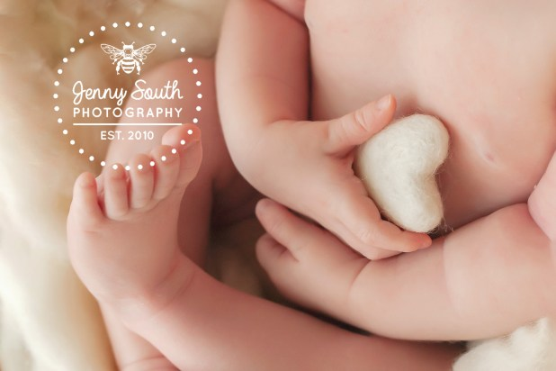 A baby girl clutches a little felt heart in her tiny fingers.