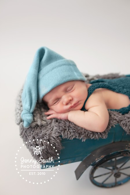 A sleepy newborn baby boy wears a nightcap whilst he cat naps in the back of a vintage toy truck.