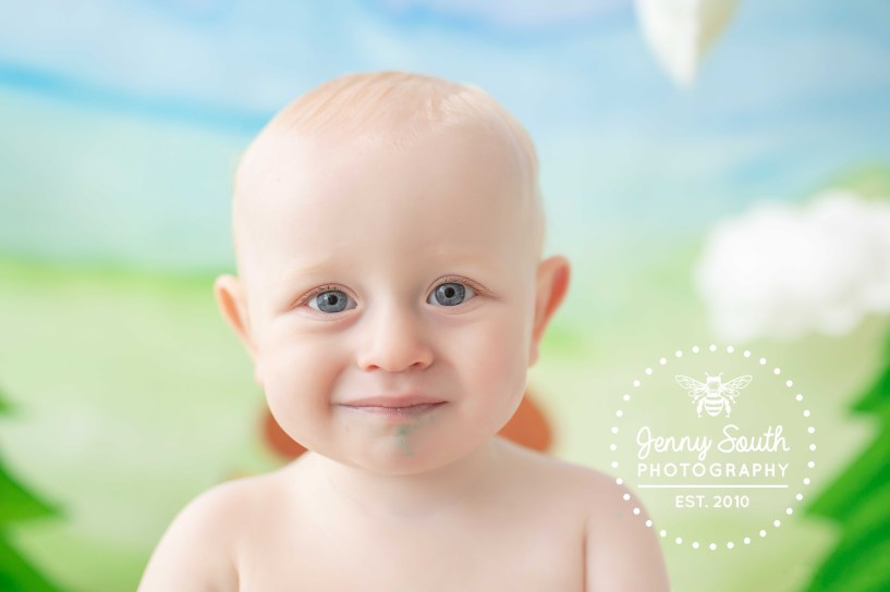 A baby boy who has just turned one smiles sweet for the camera with a mucky face of buttercream