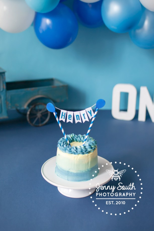 A blue and white birthday cake covered with a balloon cake top topper