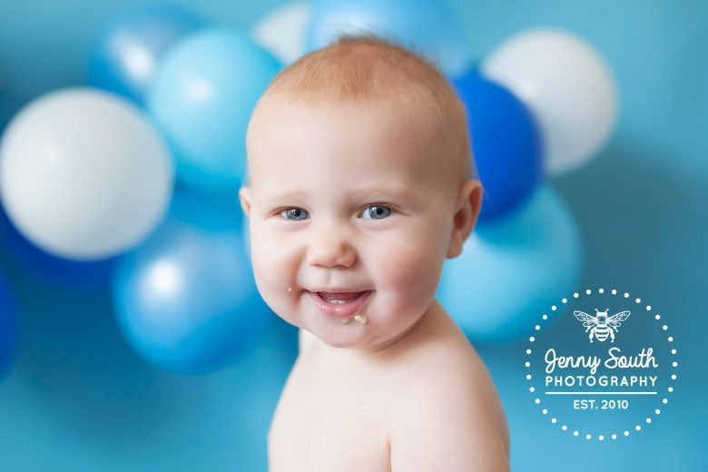 A baby boy smiles sweetly against a backdrop of a balloon wall in hues of blues
