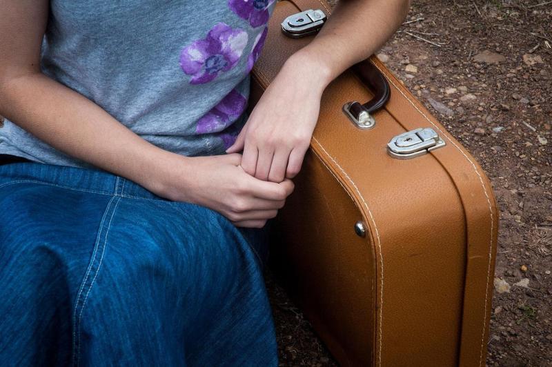 Woman sitting next to luggage