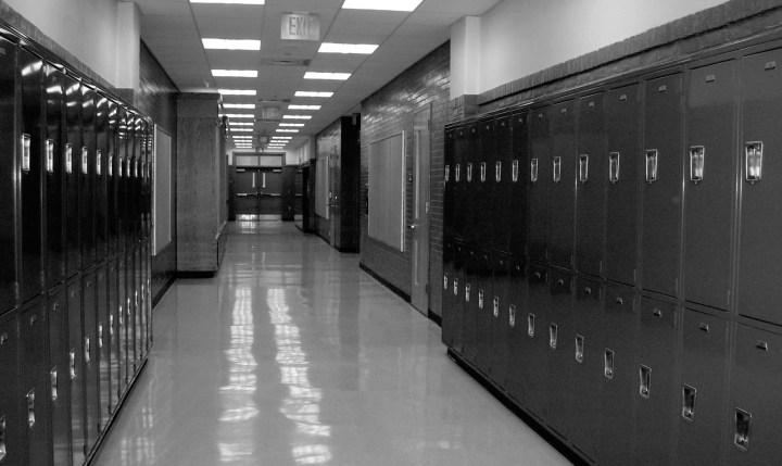 A black and white image of a school hall, with lockers lining the walls and fluorescent lights overhead