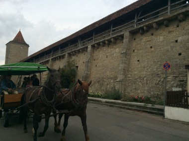 The covered walkway on the city wall behind a horse-drawn carriage