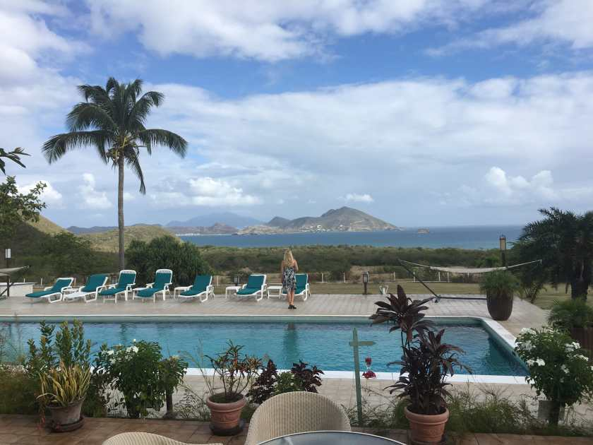 Mount Nevis Pool surrounded by palm tress with an amazing view of St. Kitts island across the narrows of the Caribbean Sea.