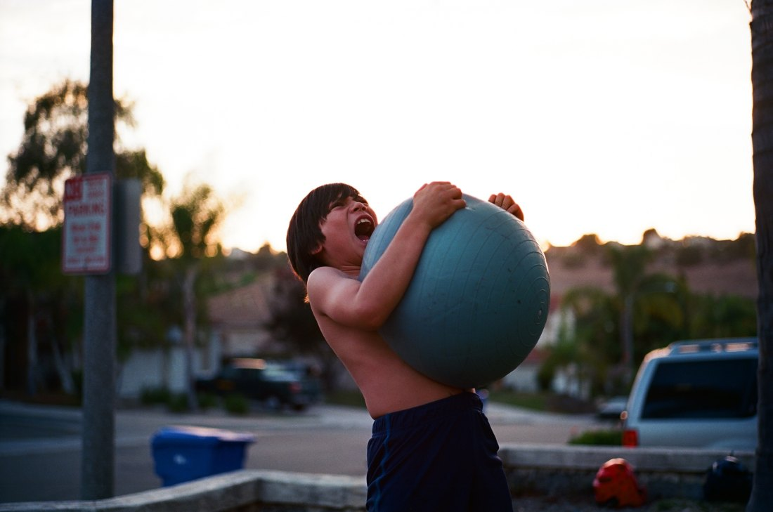 A child yelling as he picks up a weight from the ground.