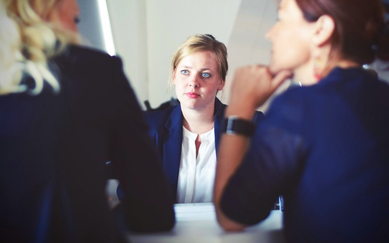 A woman sitting on one side of the table as she receives feedback from two individuals