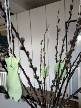 Homemade eggs, rabbits, and sheep hanging on willow branches