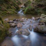 Een van de vele watervalltjes op de Ninglinspo in de Ardennen. het water kabbelt tussen rotsblokken door. De lange sluitertijd tijdens het fotograferen zorgt voor een waaiervorming patroon in het water in de voorgrond. De beboste omgeving van de rivier is mee in het beeld opgenomen.