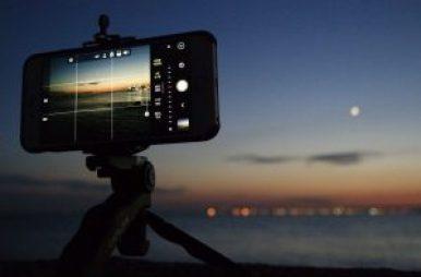 iPhone op een statief met camera-app in aanslag voor een zondsondergang