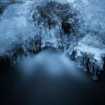 Ijspegels die boven het stromend water van de rivier Masblette hangen. Door een lange sluitertijd heeft het stromende water een melkachtige waas gekregen, wat de beweging van het water suggereert. Zowel het ijs als het water veertonen een breed scala aan blauwtinten wat het winters effect sterk beklemtoont.