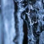 Een ijspegel waarachter water van een rotswand sijpelt. Een miniem klein vallend waterdruppeltje staat scherp op de foto en geeft de foto een leuke toets. Blauwe kleuren van het koude ijs domineren het beeld.