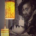 Monochroom schilderij van met de afbeelding Rubens, de kathedraal van Antwerpen en een stadszicht, verlicht met moderne beletterde doorschijnende buisvormige pendelarmaturen die een warm gelig licht uitstralen. Op de lampenkappen lees je Engelse flarden tekst.
